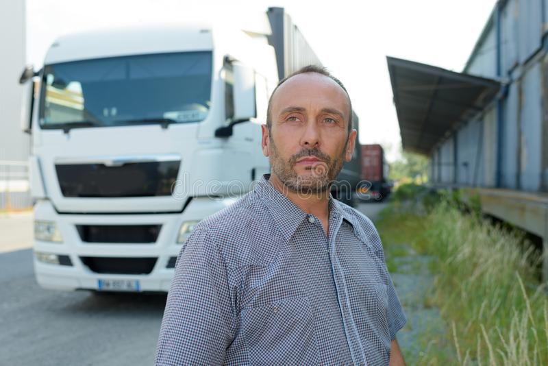 Handsome driver near modern truck outdoors. Handsome driver near big modern truck outdoors stock photography