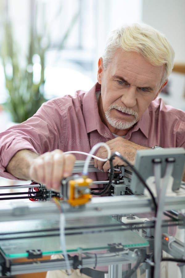 Handsome elderly man adjusting extruder of 3D printer. Important adjustments. Pleasant senior man adjusting the extruder of 3D printer while preparing it for stock photography