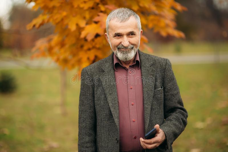 A handsome elderly man wearing glasses is using a phone. Walk in the park in autumn royalty free stock photography