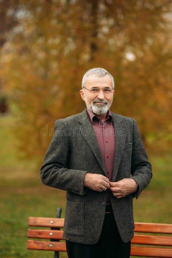 A handsome elderly man wearing glasses is using a phone. Walk in the park in autumn stock images