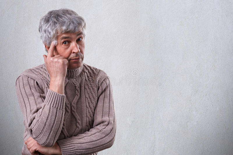 A handsome elderly man with wrinkles dressed in sweater having sad and thoughtful expression holding his finger on his temple stan stock photos