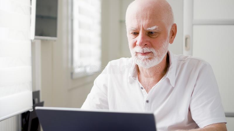 Handsome elderly senior man working on laptop computer at home. Remote freelance work on retirement stock images