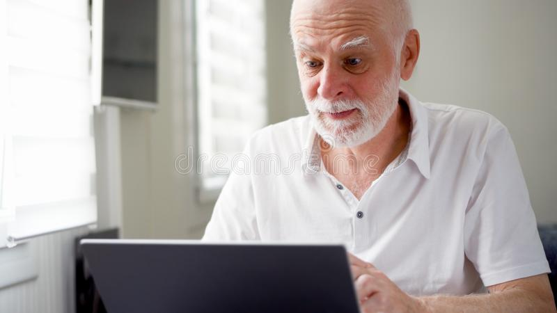 Handsome elderly senior man working on laptop computer at home. Remote freelance work on retirement royalty free stock photos