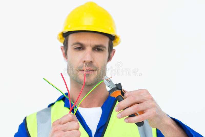Handsome electrician cutting wire with pliers stock photos