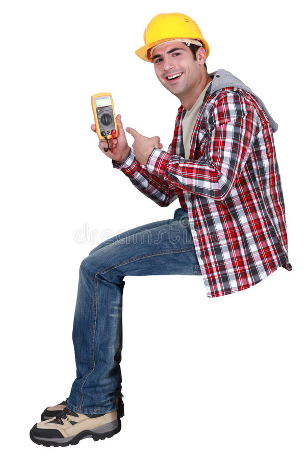 Handsome electrician pointing at tester. Young handsome electrician pointing at tester royalty free stock photos