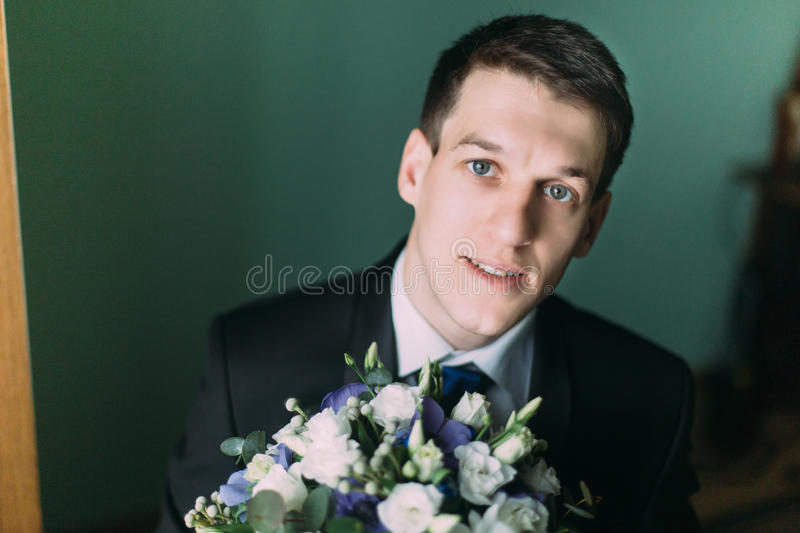 Handsome elegant groom in black suit with a wedding bouquet close-up royalty free stock images