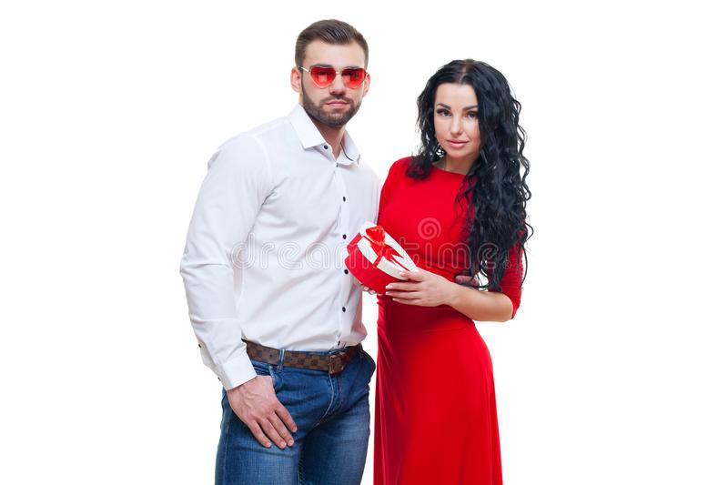 Handsome elegant guy is presenting a heart shaped gift to his beautiful girlfriend and smiling, valentines day theme royalty free stock photography