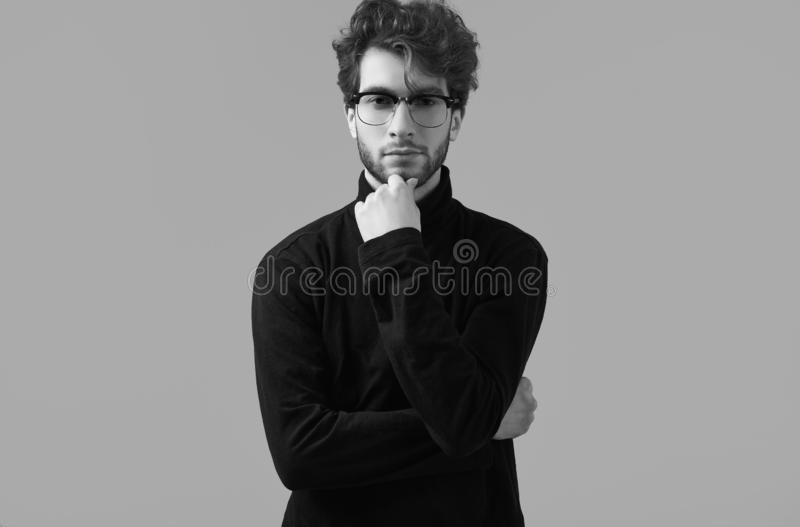 Handsome elegant man with curly hair wearing black turtleneck and glasses. Fashion portrait of handsome elegant man with curly hair wearing black turtleneck and royalty free stock photo