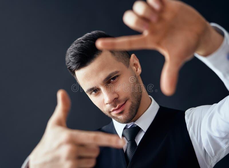 Handsome elegant man looking through a finger frame royalty free stock image