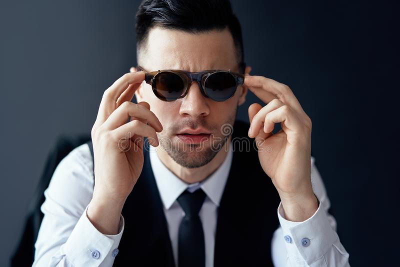 Handsome elegant man in retro sunglasses posing in studio stock photo