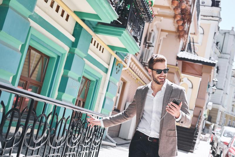 Handsome elegant young man in the street listening music from his phone stock image