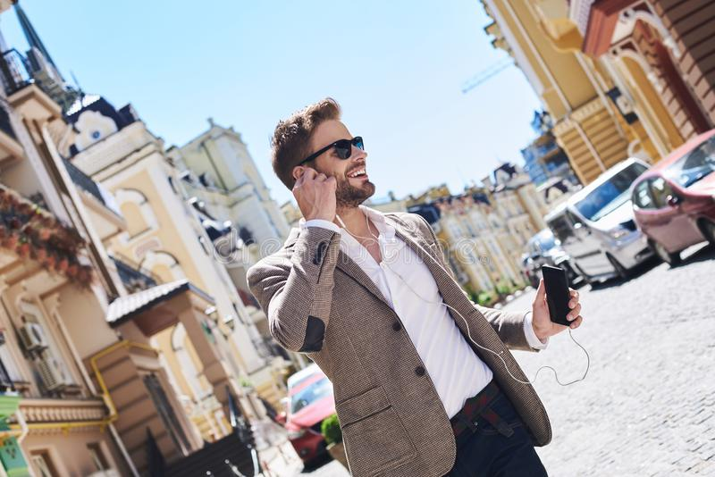 Handsome elegant young man in the street listening music from his phone stock photos