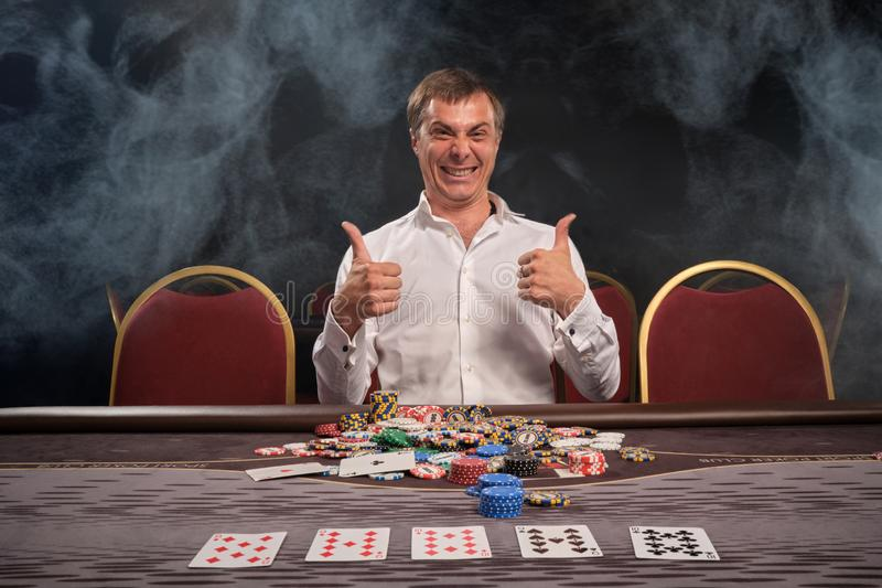 Handsome emotional man is playing poker sitting at the table in casino. royalty free stock image