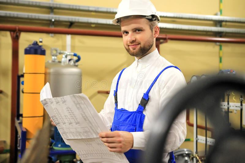 Handsome engineer with blueprints on industrial plant. Man with technical drawings on oil and gas factory royalty free stock photo