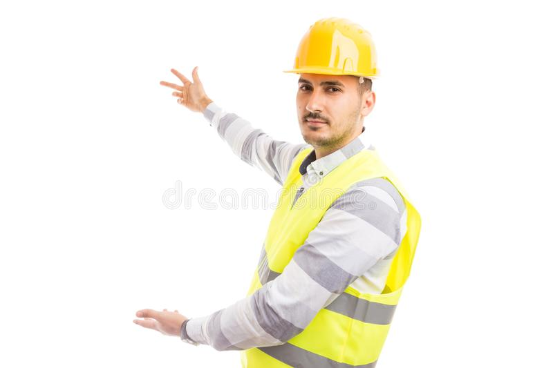 Handsome engineer or construction worker presenting white empty royalty free stock photography