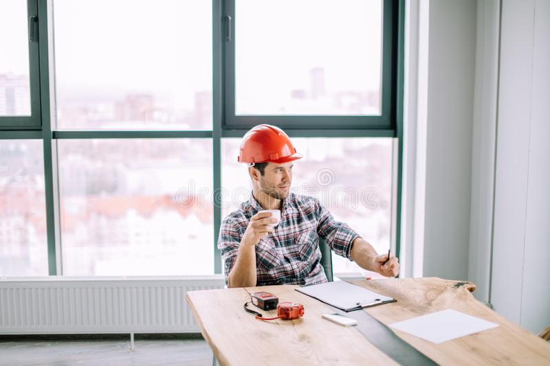 Handsome engineer is holding a cup of tea royalty free stock photos