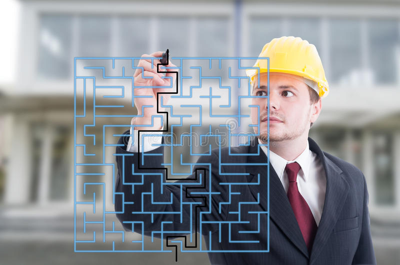 Handsome engineer solving a virtual puzzle with marker stock photo