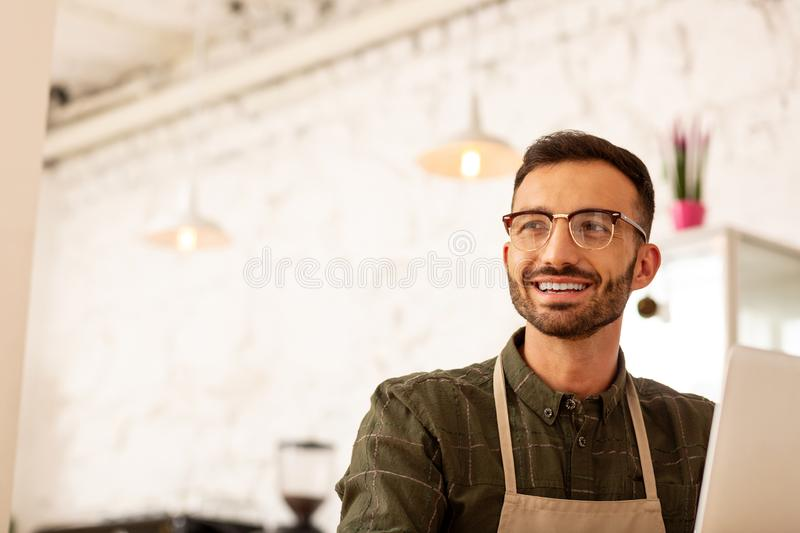 Handsome entrepreneur sitting in cafeteria with modern interior. Handsome entrepreneur. Handsome entrepreneur wearing glasses sitting in cafeteria with modern stock photos