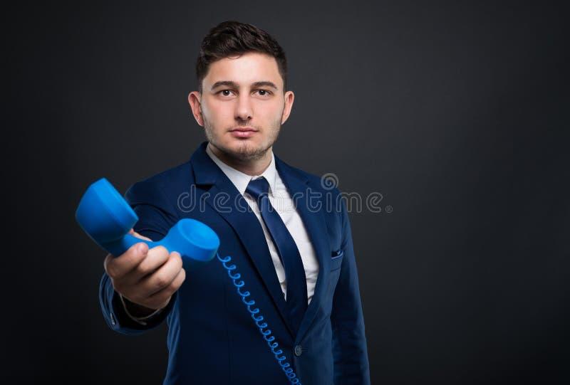 Handsome entrepreneur talking on telephone. Handsome entrepreneur talking and holding the telephone royalty free stock photo