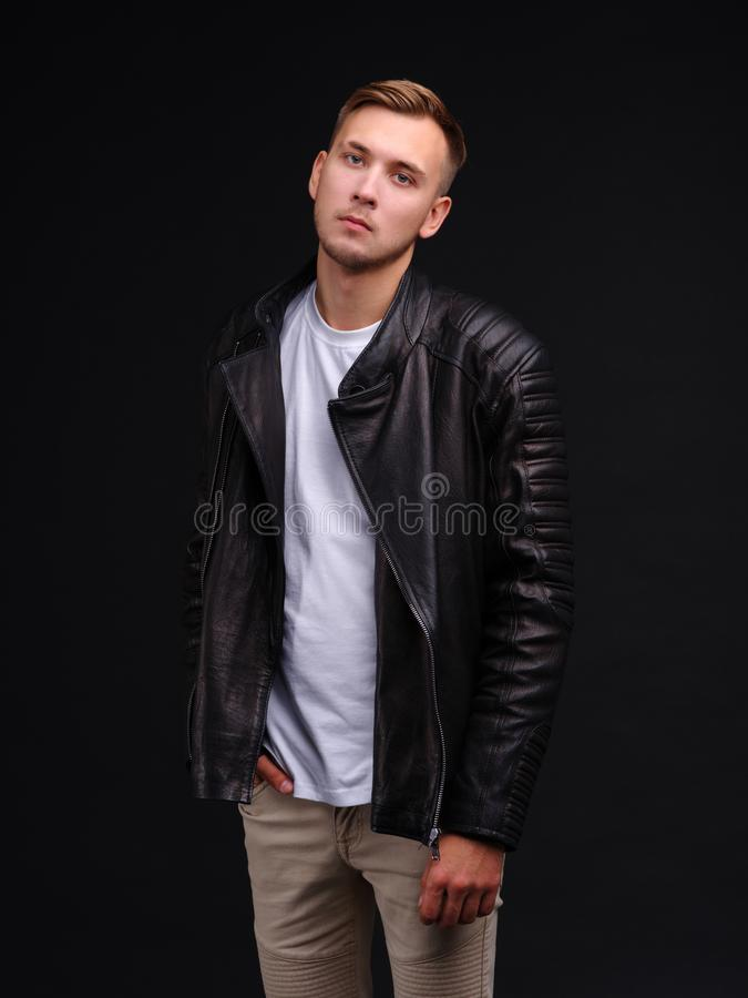 A guy in a T-shirt and black leather jacket and looks with a serious look. royalty free stock photos