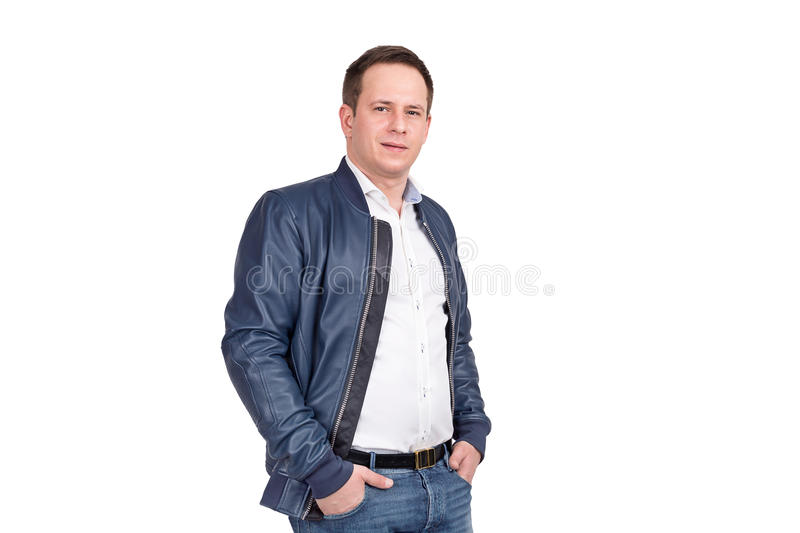 handsome european man white shirt  blue jeans leather jacket holding hands pockets standing against ba royalty free stock images