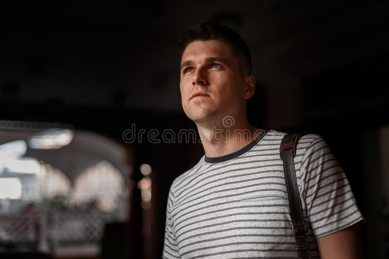 Handsome European young man with a trendy hairstyle in a stylish striped t-shirt with a leather bag on shoulder is standing royalty free stock photography