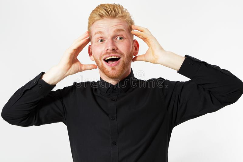 Handsome excited surprised red hair man happy smile looking at camera, hold hands on head, young guy wear black stylish shirt, royalty free stock photo