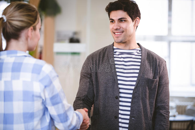 Handsome executive shaking hands with colleague at creative office royalty free stock photos