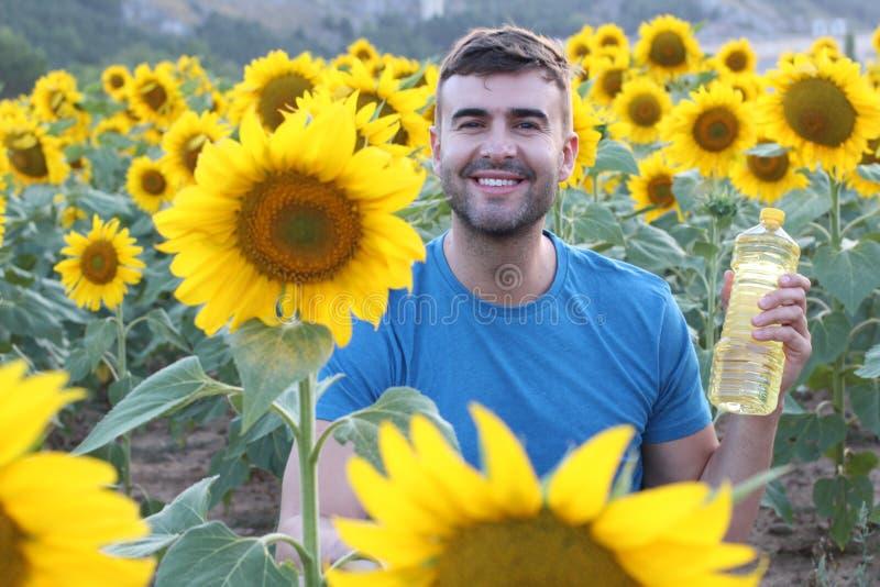 Handsome farmer holding sunflower oil bottle stock photo