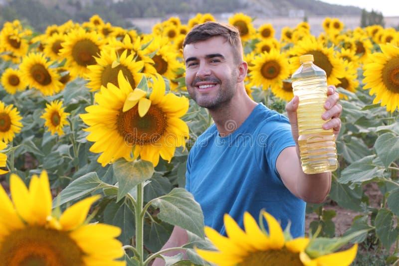 Handsome farmer holding sunflower oil bottle royalty free stock photos