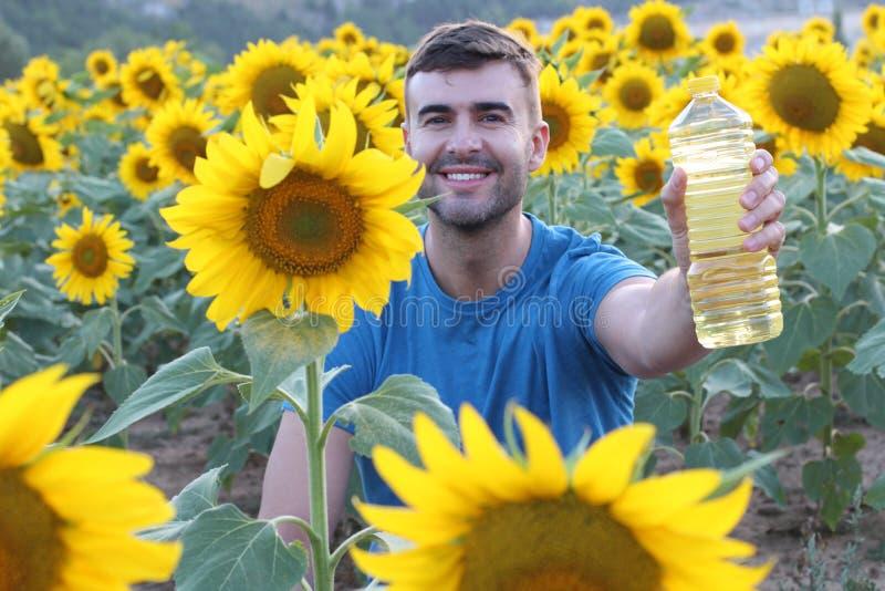 Handsome farmer holding sunflower oil bottle stock photography