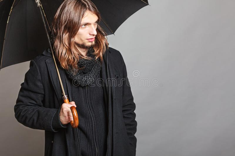 Handsome fashion man portrait wearing black coat. Portrait of handsome fashionable man wearing black coat and scarf holding umbrella. Young guy posing in studio stock photos