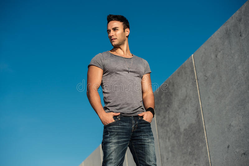 Handsome fashion model man posing outdoors wearing grey t-shirt and jeans royalty free stock photo