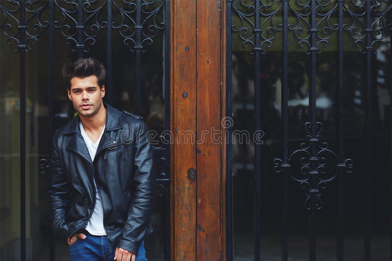 Handsome fashionable male in trendily clothing posing outdoors in the city royalty free stock photography