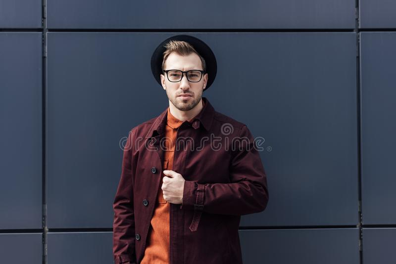 Handsome fashionable man in black standing. At black wall stock photography