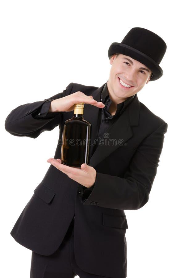 Retro stylish man demonstrates bottle with alcohol royalty free stock photo