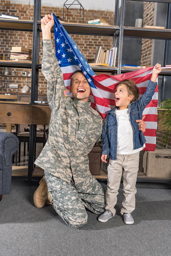 handsome father in army uniform and son with big usa flag stock photography