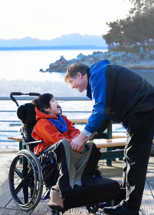 Handsome father talking with disabled biracial son outdoors royalty free stock images