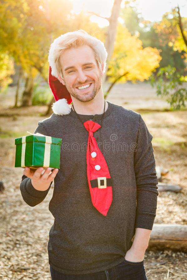 Handsome Festive Young Caucasian Man Holding Christmas Gift Outdoors royalty free stock images