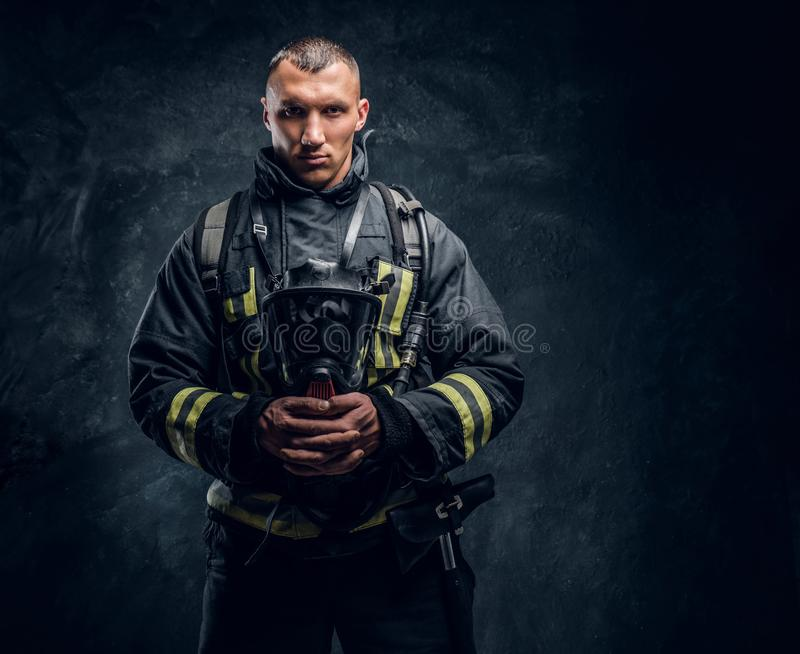 A handsome fireman wearing protective uniform holding an oxygen mask and looking at a camera. royalty free stock image