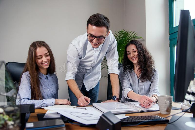 Handsome firm manager in glasses explains work tasks for his employees. Creative people or advertising business concept. Young firm manager explains work tasks royalty free stock image