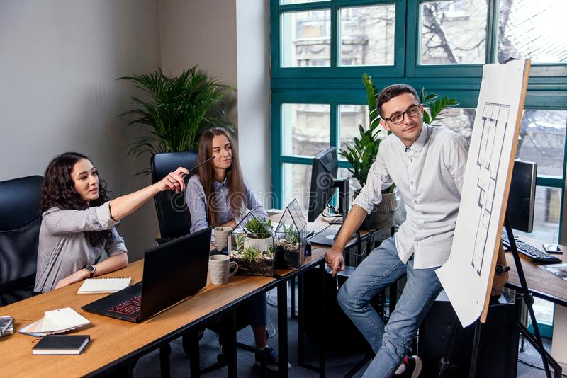 Handsome firm manager in glasses explains work tasks for his employees. Creative people or advertising business concept. Young firm manager explains work tasks stock photography