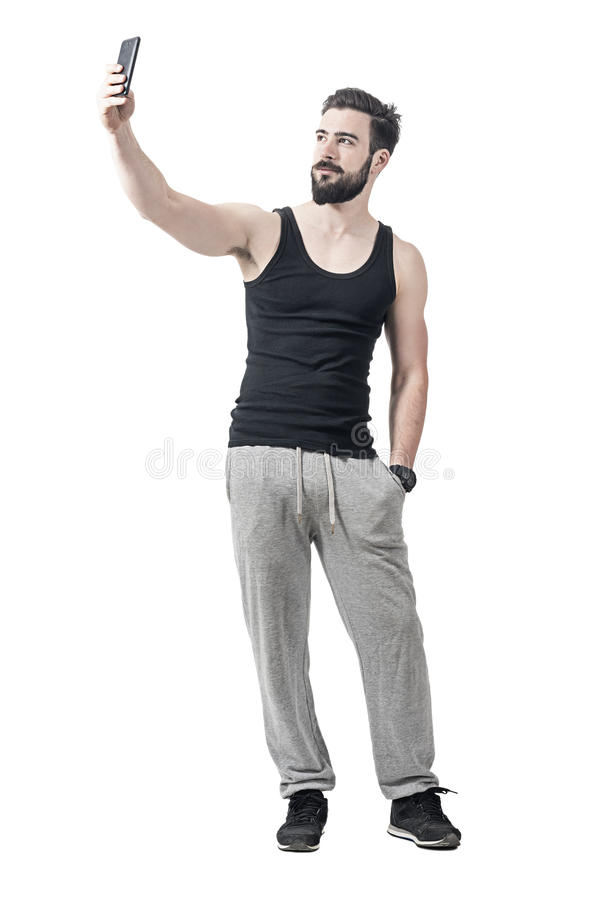 Handsome fit bearded young man taking selfie with mobile phone. Full body length portrait isolated over white studio background royalty free stock photography