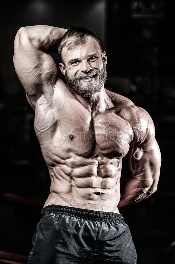 Handsome fit caucasian muscular man flexing his muscles in gym stock photography