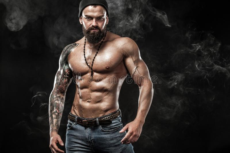 Handsome fit man posing wearing in jeans with tattoo. Sport and fashion concept isolated on black background. stock photo