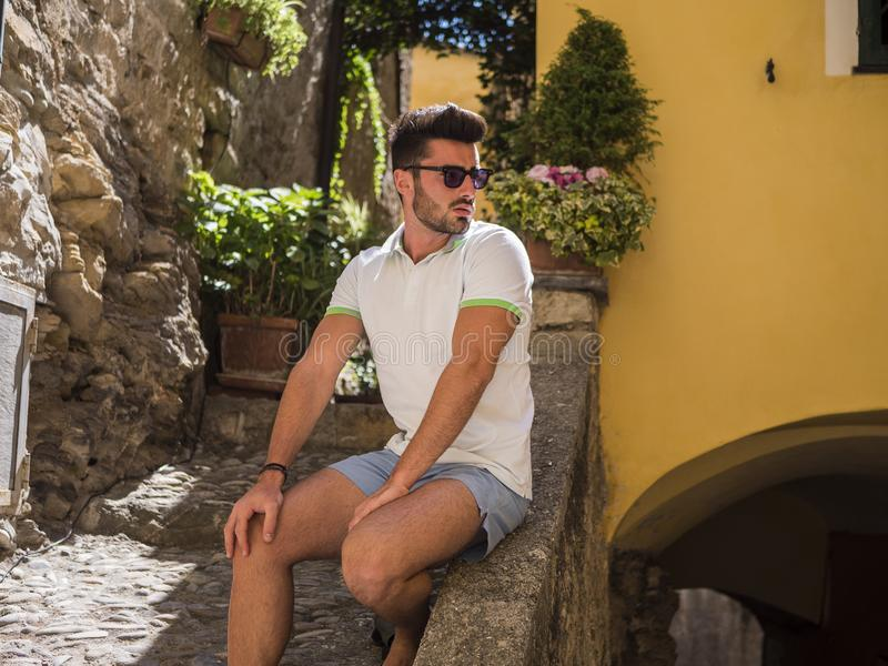Handsome man sitting at seaside town stock photography