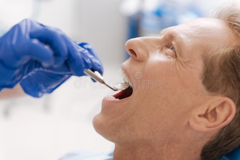 Handsome fit man undergoing dental examination in clinic stock photo