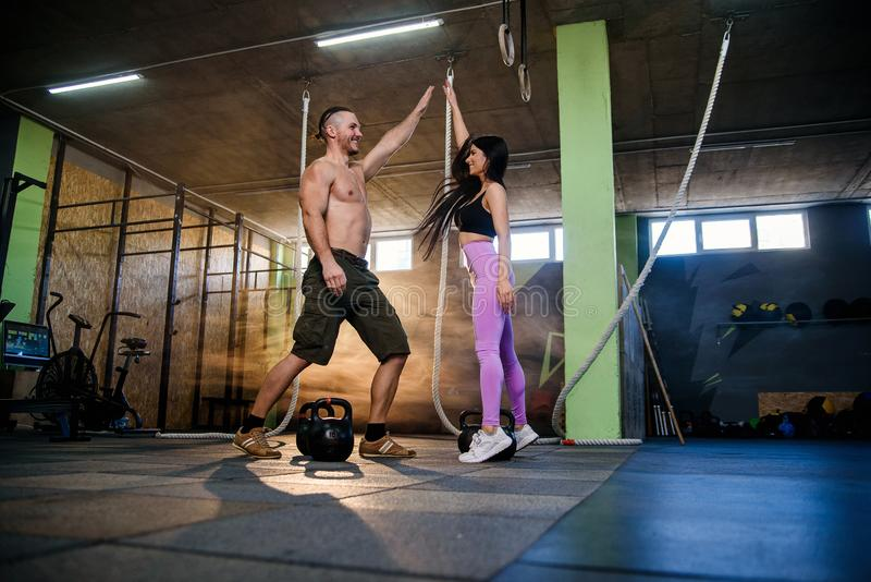 Handsome fit woman and man giving each other hight five after hard successful training in the gym. royalty free stock images