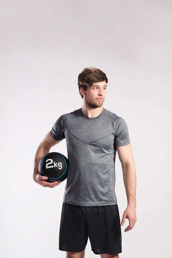 Handsome fitness man holding medicine ball, studio shot. royalty free stock photography