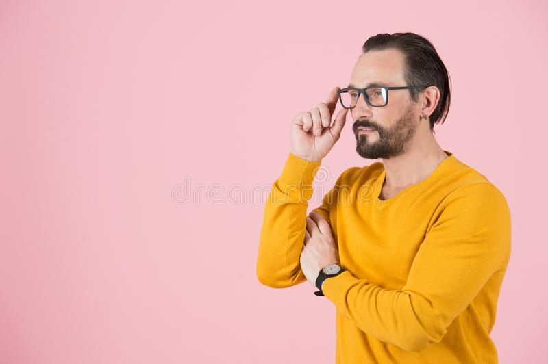 Handsome freelancer wearing glasses looking off to right of the frame. Man with glasses searching analytical expression stock photo